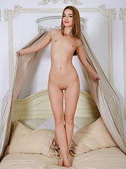Nicole May bares her sexy, petite body as she poses on the bed.