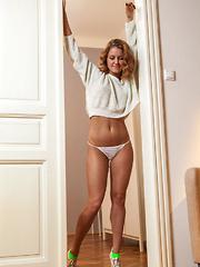 Evridika bares her slender body as she strips indoors.