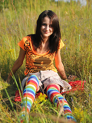 Wonderful teen beauty in long striped socks taking off her clothes outdoors in the field.