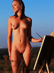 Gorgeous beauty showing tempting nude body while drawing a picture outdoors in the field.