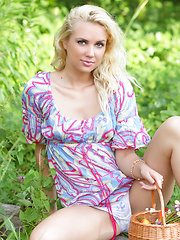 Perfect blonde teen girl with a basket of peaches taking off clothes and spreading outdoors.