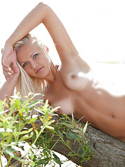 Wonderful shapely blonde beauty spreads legs revealing alluring shaved cunt on the coast.