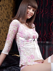 Alluringly slim and slender Candy Rose attractively naked and sprawled on the bed and stripping her flowery dress, baring her sweet and smooth assets with a charming smile.