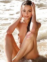 Lorena is young and beautiful girl with slick and wet slippery body as she plays on the beach.