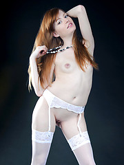 White thigh-high stockings and a matching lace garter belt amplifies Jo\'s innocent and youthful allure, with her smooth, fair skin, pink and puffy details, and a sweet smiling face.