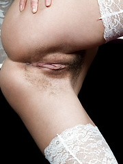 Wearing a white thigh-high stocking that accentuates her legs perfectly, and matching black lingerie