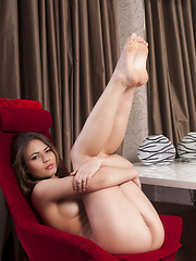 Liana raises the room's temperature with   a sensual striptease of her nightwear   and poses seductively on the chair in   her debut series.