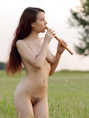 Beautiful long haired honey with juicy breasts posing in the nude outdoors in the field.