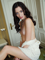Sultry, seductive face framed by curled brown hair, a teasing smile, and lots of open, explicit poses that showcase Zsanett Tormay's slender build, smooth fair skin, and delicious pink pussy with puffy clit