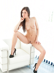 Petite bombshell Caprice A posing seductively in her black body-hugging lingerie dress and sparkly stiletto heels.