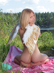 Amazing blonde teen babe gets naked on the lap of nature and tries to mimic some angelic beauty with her poses.